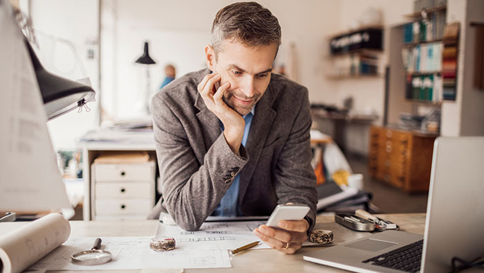 Mann sieht am Schreibtisch lehnend auf sein Smartphone