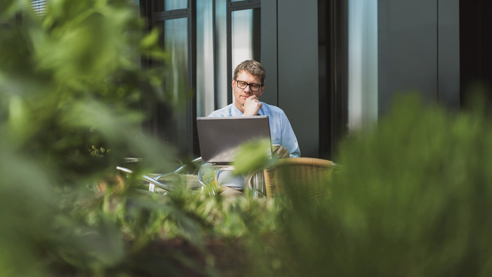 Angestellter arbeitet draußen an seinem Laptop.