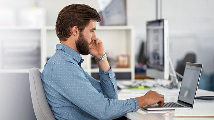 Businessman im blauen Hemd arbeitet mit MacBook