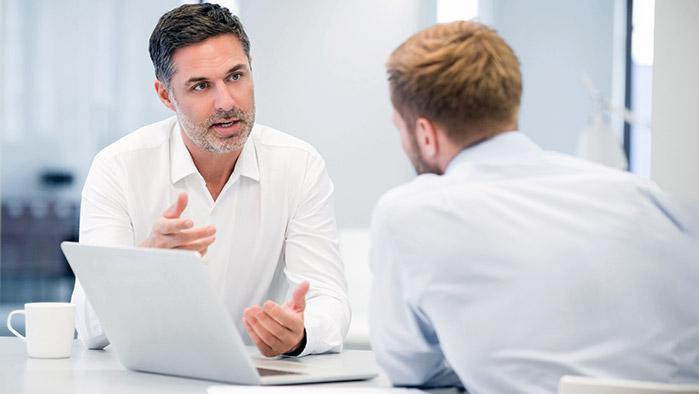 Zwei Businessmänner unterhalten sich in einer Besprechung