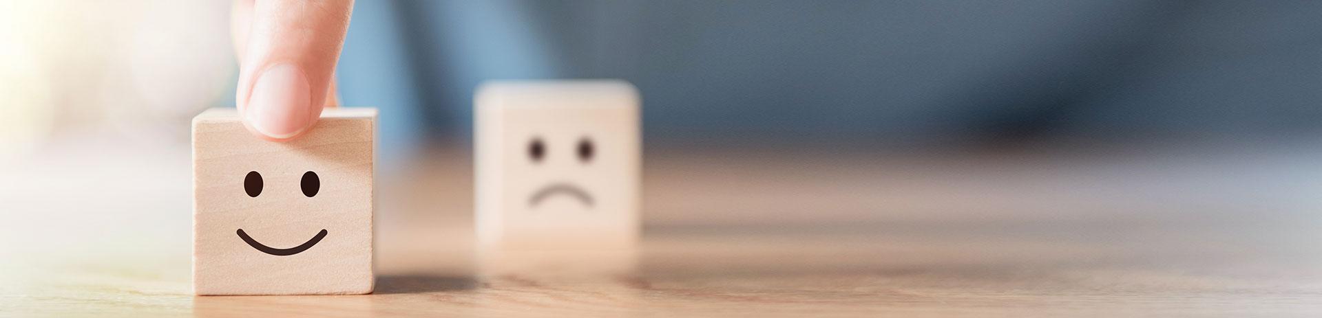Wählen zwischen einem Smiley-Gesicht & unscharfen bedrückten Gesichtssymbol auf Holz Würfel