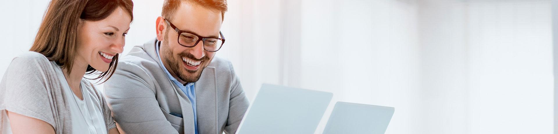 Geschäftsleute sitzen an Besprechungstisch vor Computer
