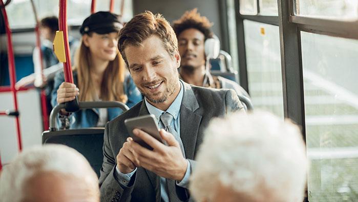 Mann sitzt im Bus und arbeitet mit seinem Smartphone