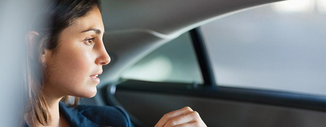 Business Frau sitzt auf Rücksitz eines Autos und sieht aus dem Fenster
