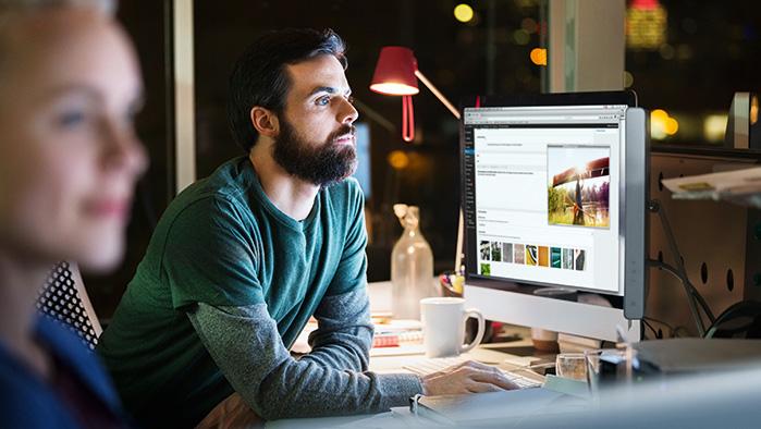 Mann mit Brille und Bart arbeitet am Schreibtisch und sieht in einen Bildschirm.