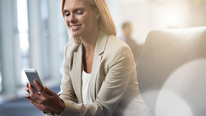 Geschäftsfrau sitzt bequem in einem Foteu Sessel und bedient ihr Smartphone mit einem Lächeln im Gesicht.