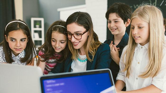 Schüler arbeiten mit Lehrerin im Klassenzimmer mit Laptops