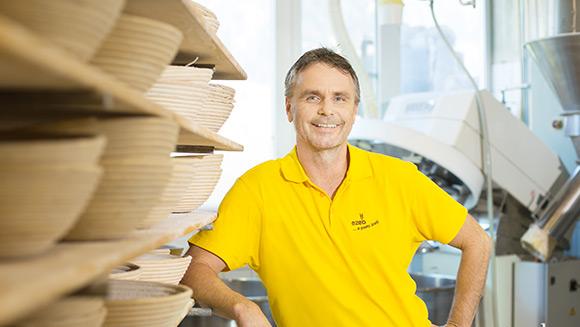 ein Mann in gelbem T-Shirt mit dem ezeb-Logo lehnt sich an ein großes Regal, das voller Brotkörbe ist; im Hintergrund sieht man einen industriellen Mixer