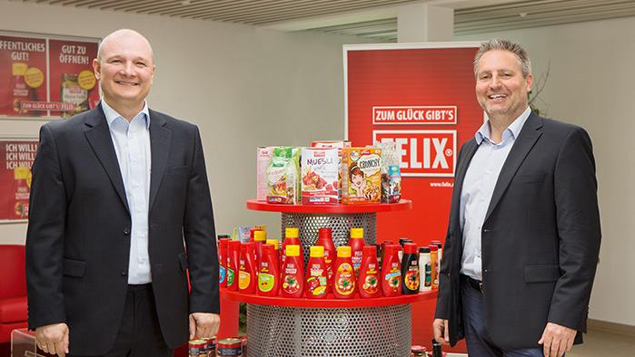 zwei Personen im Anzug stehen vor einem Produktregal gefüllt mit FELIX-Produkten
