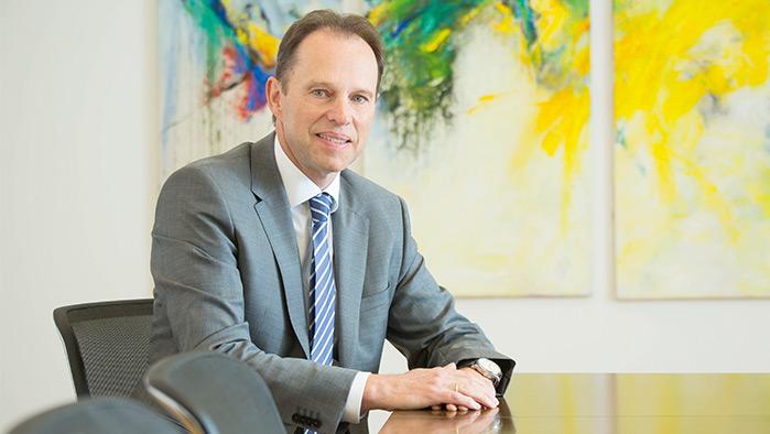 Mann im Anzug sitzt in einem Besprechungszimmer