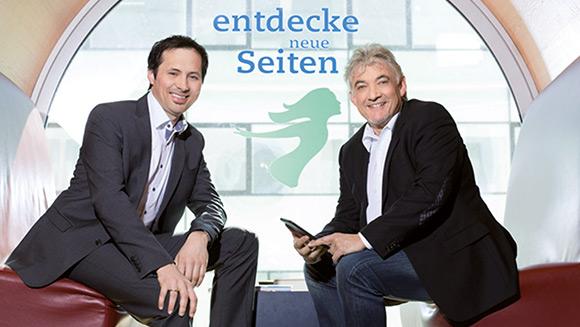 ein junger Herr auf der linken und ein älterer Herr auf der rechten Seite sitzen sich auf roten Bänken gegenüber; hinter ihnen steht auf einem Fenster