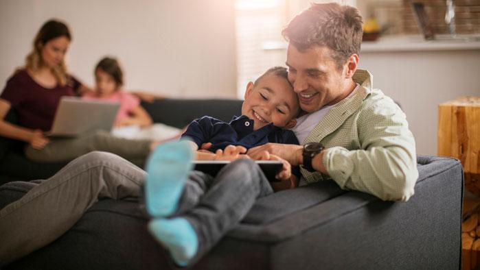 Familie, die kabellos auf Tablet und Laptop surft