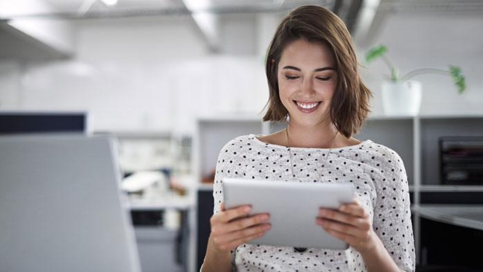 Frau im Büro, die etwas auf einem Tablet liest