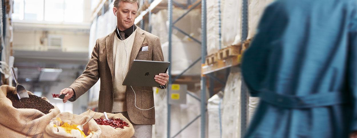 Mann mit iPad in Gewürzmittel-Lagerhalle