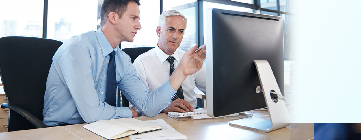 Mann zeigt anderem Business-Mann etwas am Bildschirm