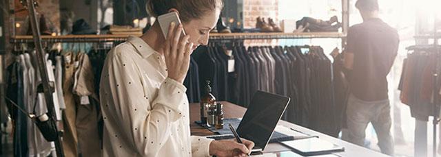 Verkäuferin in einem Kleidershop telefoniert mit Smartphone