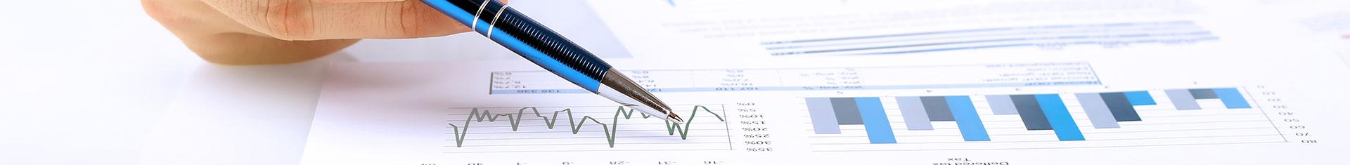 statistische Grafik auf einem Bildschirm; mit einem Kuli wird ein Punkt darin markiert