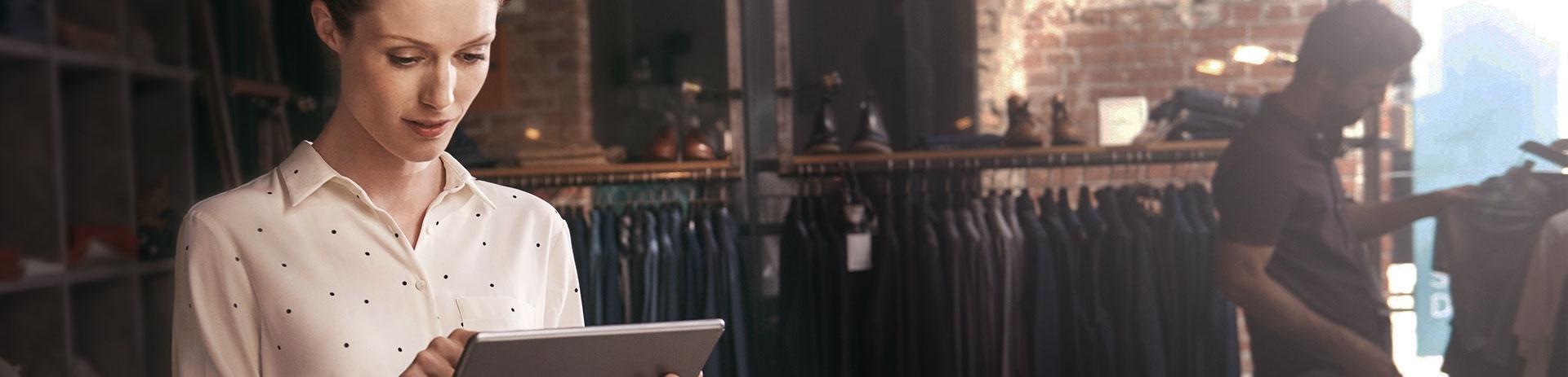 Verkäuferin in Gewandshop bedient Tablet