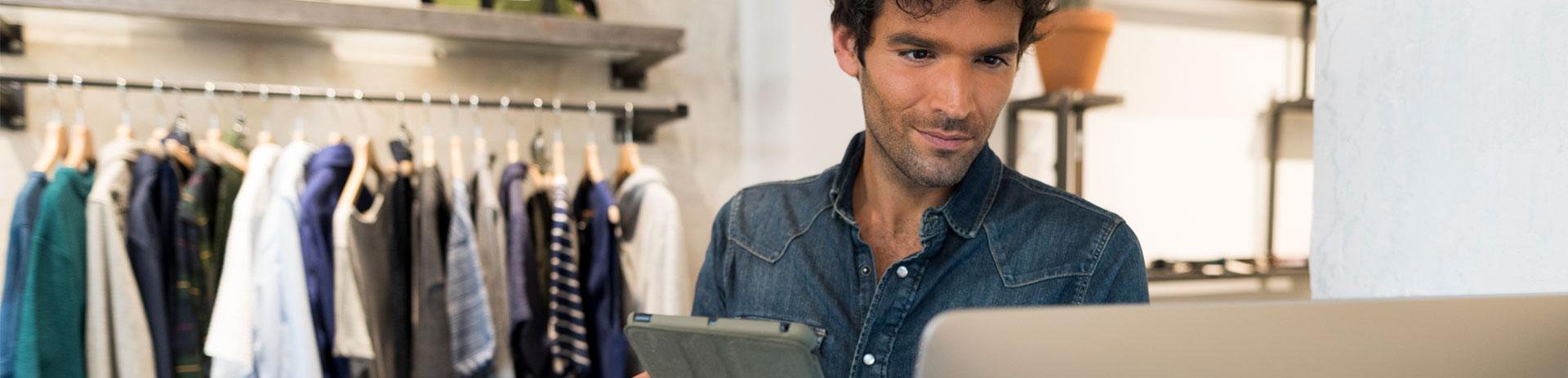 Verkäufer in Modegeschäft sieht auf Bildschirm