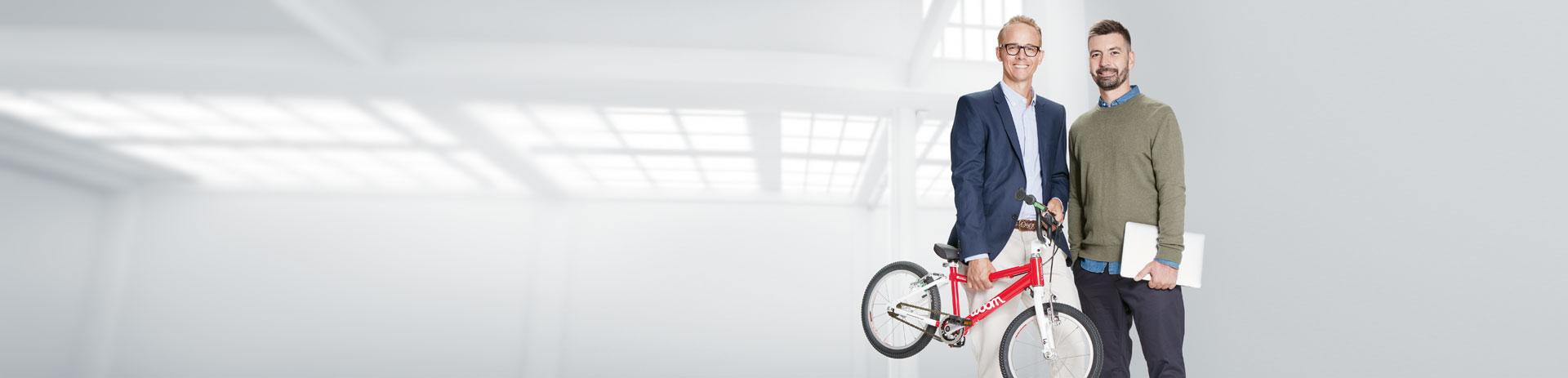 Zwei Business-Leute stehen mit Kinderrad und Notebook in einer Fabrikhalle