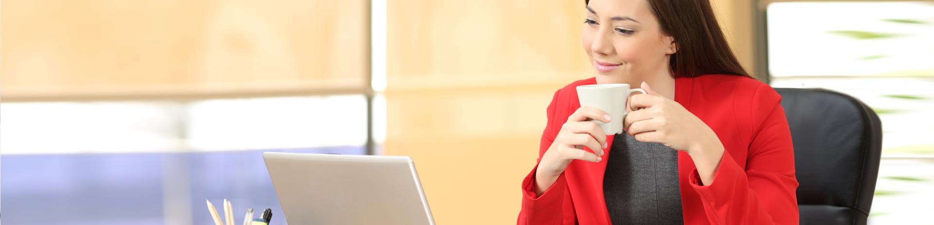 Frau, die im Büro vor dem Laptop sitzt