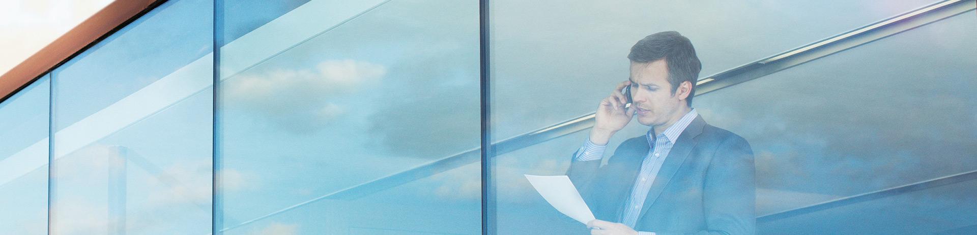 man sieht von außen in ein Bürogebäude; dahinter steht ein Mann, der telefoniert und einen Zettel in der Hand hält