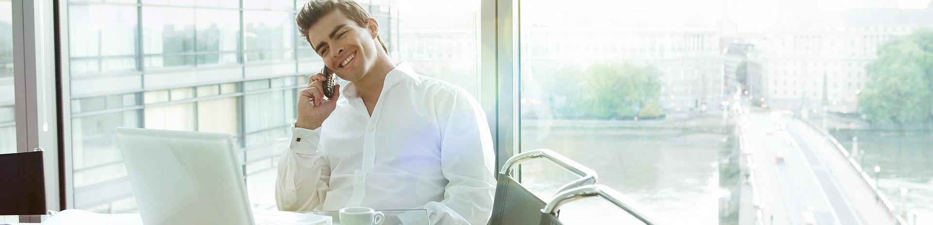 ein Mann im Hemd gekleidet, sitzt am Esstisch mit seinem Laptop und telefoniert. Im Hintergrund sieht man eine Brücke, die über einen Fluss führt.