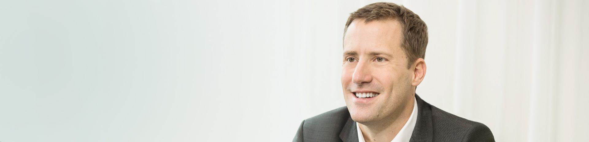ein Mann im Anzug vor einem hellen Hintergrund
