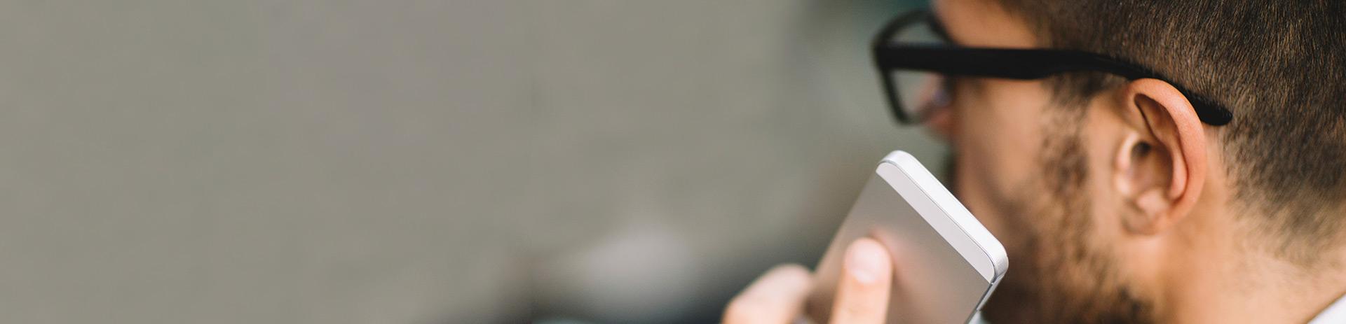 Profil eines Mannes, der ein Mobiltelefon Richtung Ohr führt