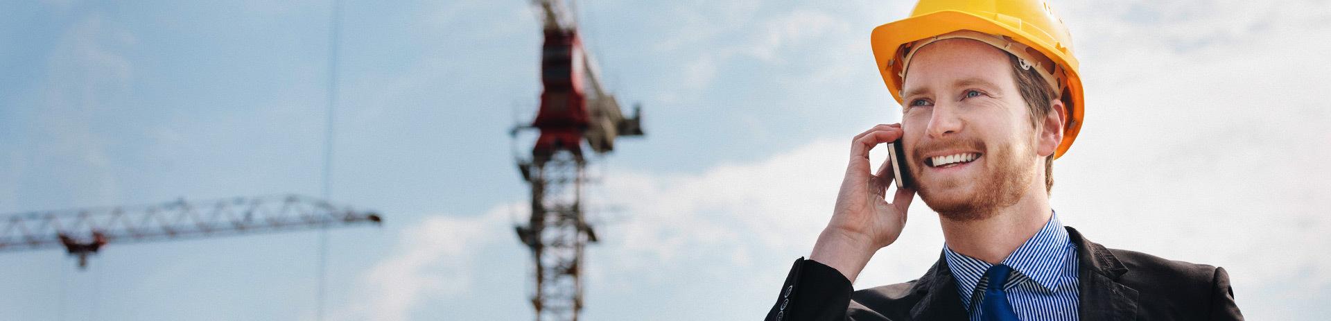 Telefonierender Bauunternehmer mit Baukränen im Hintergrund