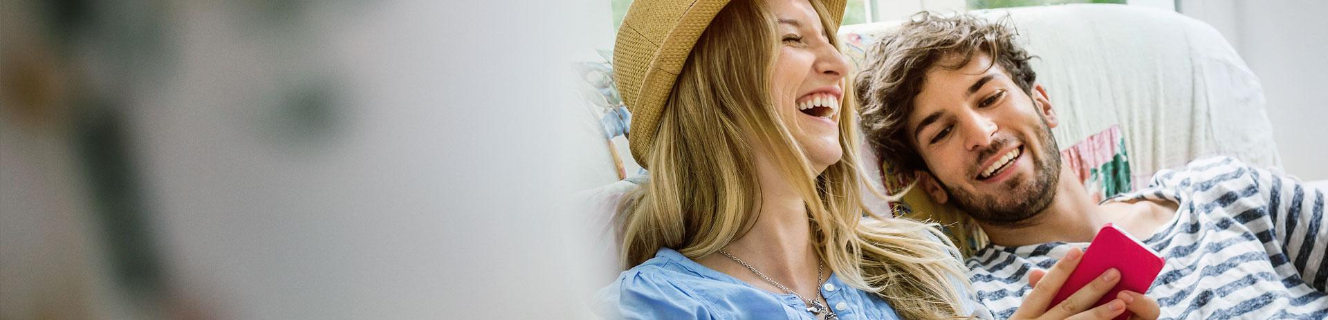 Lachende Frau, die ein Handy hält und ein lachender Mann