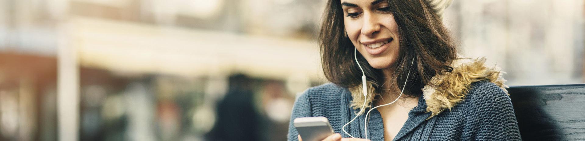 Junge Frau mit Handy und Kopfhörern