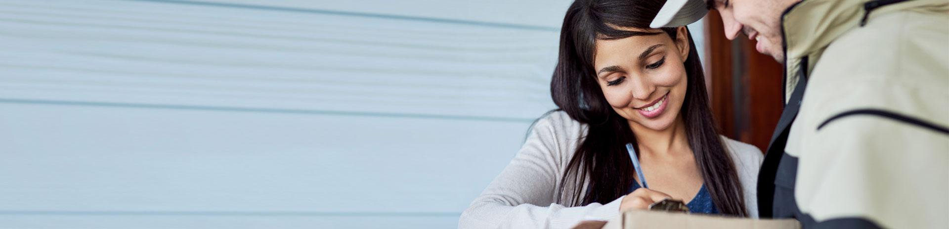 Frau unterschreibt gluecklich die Uebernahme eines Pakets, die gesteigerte Kundenorientierung und Effizienz durch A1 Software- und Telco-Loesungen betonend.