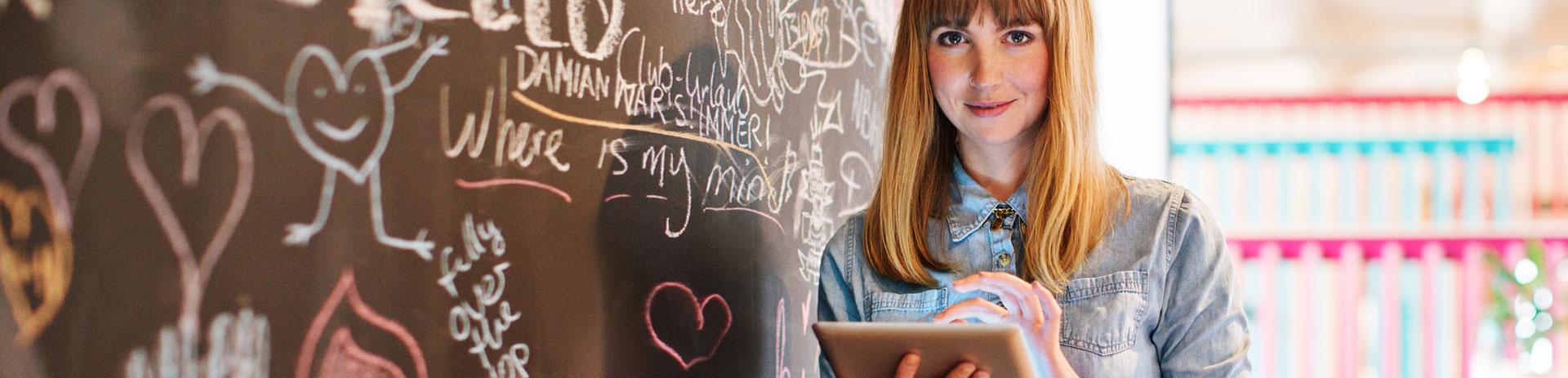 Frau beschaeftigt sich mit Tablet. Sie hat ein Unternehmen gegruendet und hat mit den guenstigen Angeboten von A1 rund um SaaS, Internet und Mobiltelefonie alles was sie braucht aus einer Hand. Ihr Start-up ist ein voller Erfolg.