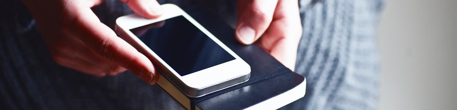 Handy liegt auf Notizbuch.