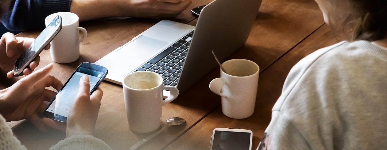 Arbeitskollegen, die während eines informellen Meetings auf ihren Smartphones arbeiten