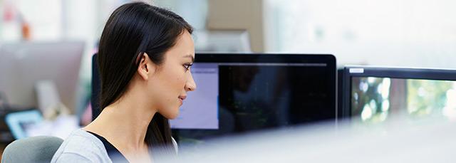 junge Frau sitzt vor einem Bildschirm