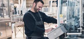 Mann bedient laechelnd eine Maschine und symbolisiert die Effektivitätssteigerung durch branchenspezifische Produktloesungen von A1.