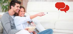 Päärchen sitzt mit Popcorn vor dem Fernseher