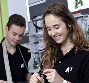 zwei junge Lehrlinge lernen von ihrem Lehrer ein Gerät zu bedienen