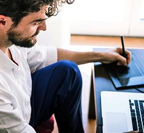 Mann arbeitend mit Macbook und paintboard