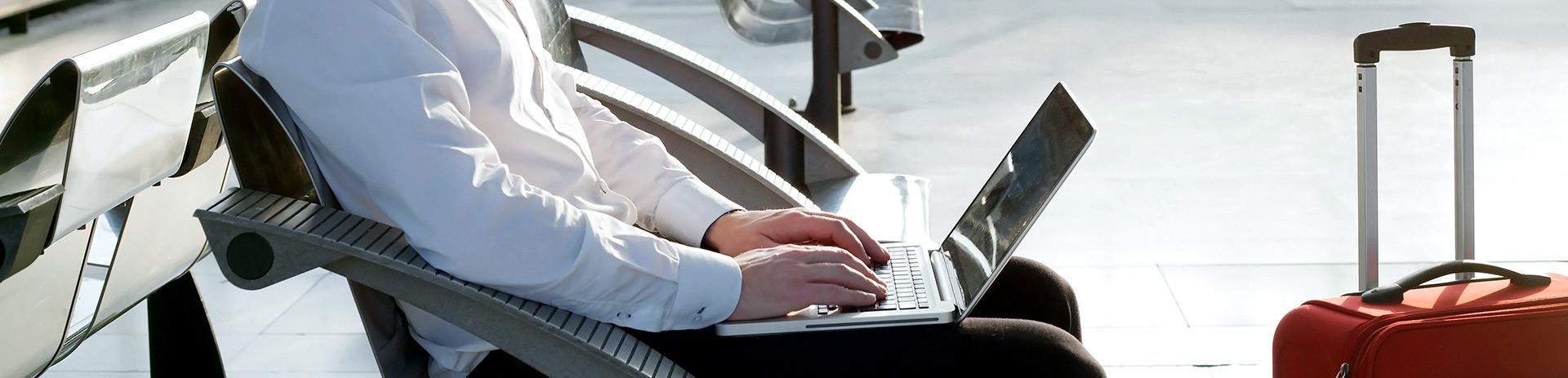 Businessmann am Flughafen mit Laptop