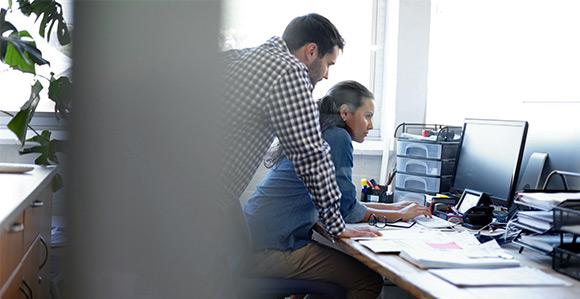Mann und Frau am Arbeitsplatz vor PC