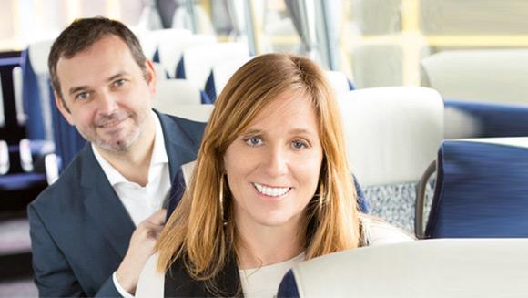 eine Dame und ein Herr lächeln in die Kamera und sitzen dabei hintereinander in einem Reisebus mit blauen Sitzen