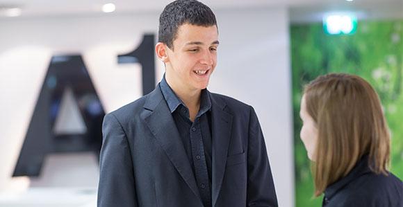 eine junger Mann, in einem Anzug gekleidet steht vor einer Frau; im Hintergrund das A1 Logo