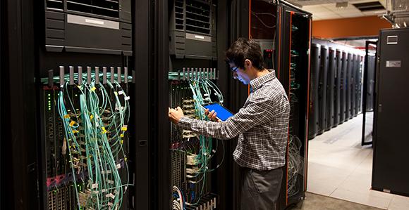 ein Mann steht mit einem Tablett in der Hand in einer Server-Farm und kontrolliert unterschiedliche Anschlüsse