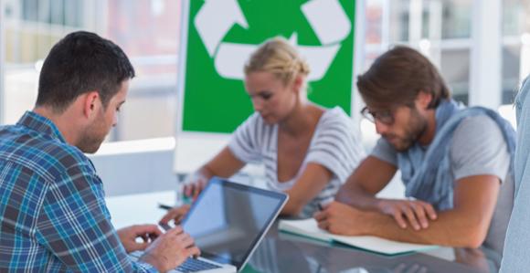 Drei Personen sitzen an einem Tisch und arbeiten; im Hintergrund sieht man das Recycling-Zeichen - drei Pfeile, die ein Dreieck bilden