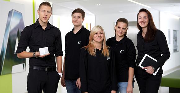 3 weibliche und 2 männliche junge Mitarbeiter von A1 sind einheitlich schwarz gekleidet und stehen vor einer Werbewand von A1