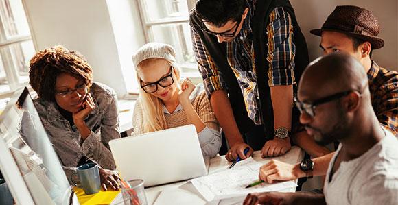 5 Personen unterschiedlichen Geschlechts und Herkunft sitzen an einem Arbeitsplatz und arbeiten gemeinsam an einem Projekt