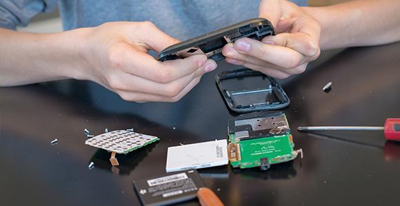 ein Mann zerlegt ein Handy in seine Einzelteile